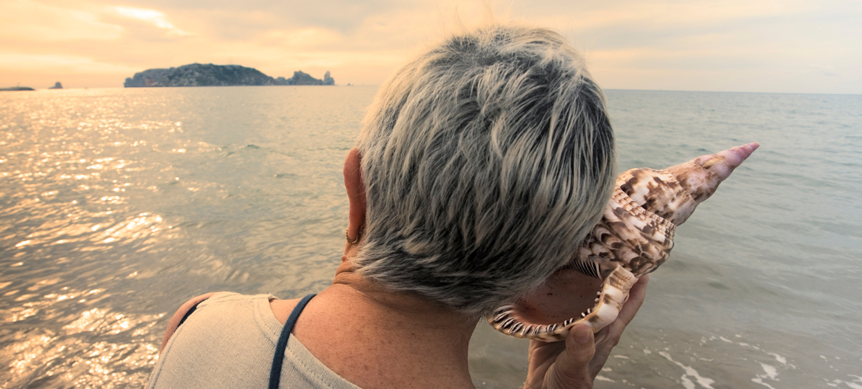 Woman listening to conch shell